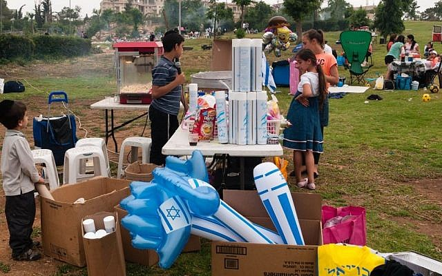 Children sell Independence Day paraphernalia in Jerusalem's Sacher Park on Tuesday, May 6, 2014. (photo credit: Yifa Yaakov/The Times of Israel)