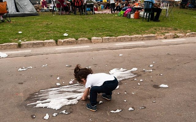 "A child plays with the white spray known as ""snow,"" which is used on Independence Day, in Jerusalem's Sacher Park, Tuesday, May 6, 2014. (photo credit: Yifa Yaakov/The Times of Israel)"