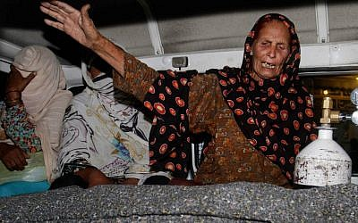 A family member of a pregnant woman who was stoned to death by her own family wails over her dead body in an ambulance at a local hospital in Lahore, Pakistan, Tuesday, May 27, 2014. (photo credit: AP/K.M. Chaudary)
