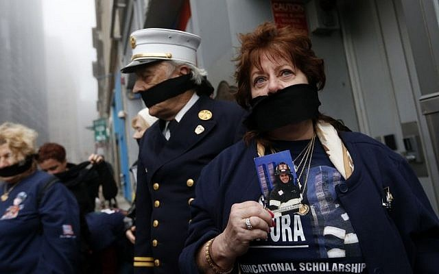 Maureen Santora holds a photo of her son, firefighter Christopher Santora, as she and other family members of victims of the of the Sept. 11, 2001 attacks wear black gags over their mouths in protest of the transfer of unidentified remains of those killed at the World Trade Center from the Office of the Chief Medical Examiner to the World Trade Center site, Saturday, May 10, 2014, in New York. (Photo credit: AP/Jason DeCrow)