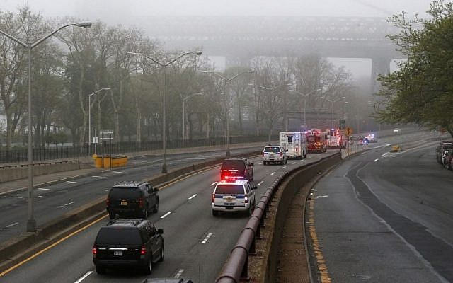 Part of the Williamsburg Bridge peeks through thick morning fog as police and fire department vehicles lead a procession along Franklin D. Roosevelt East River Drive with the unidentified remains of victims of the Sept. 11, 2001 attacks as they are returned to the World Trade Center site, Saturday, May 10, 2014, in New York. (Photo credit: AP/Julio Cortez)