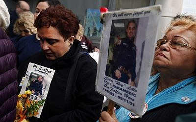 Iliana Flores, left, and her mother Ilia Rodriguez hold photos of Carlos Lillo, Iliana's brother and Ilia's son, as they join other family members of victims of the of the Sept. 11, 2001 attacks in protest of the transfer of unidentified remains of those killed at the World Trade Center from the Office of the Chief Medical Examiner to the World Trade Center site, Saturday, May 10, 2014, in New York. (Photo credit: AP/Jason DeCrow)