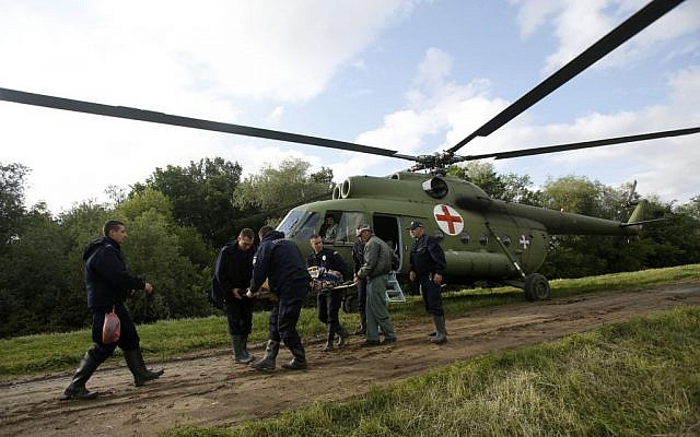 Serbian police officers carry an old woman from a military helicopter during evacuation from Obrenovac, some 30 kilometers (18 miles) southwest of Belgrade Serbia, Saturday, May 17, 2014. Record flooding in the Balkans leaves at least 20 people dead in Serbia and Bosnia and is forcing tens of thousands to flee their homes. Meteorologists say the flooding is the worst since records began 120 years ago. (photo credit: AP/Darko Vojinovic)