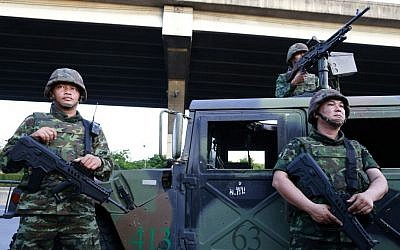 Thai soldiers take up position on a street outside the Centre for the Administration of Peace and Order (CAPO) after soldiers were sent in to seize the center Tuesday, May 20, 2014 in Bangkok, Thailand. (photo credit: AP Photo/Wason Wanichakorn)