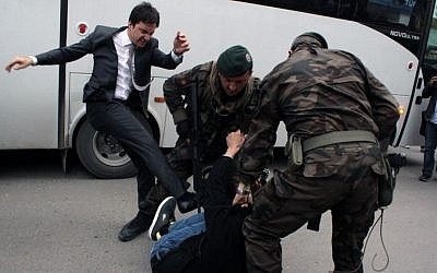 A person identified by Turkish media as Yusuf Yerkel, adviser to Turkish Prime Minister Recep Tayyip Erdogan, kicks a protester already held by special forces police members during Erdogan's visiting Soma, Turkey, on May 14, 2014. (photo credit: AP Photo/Depo Photos)