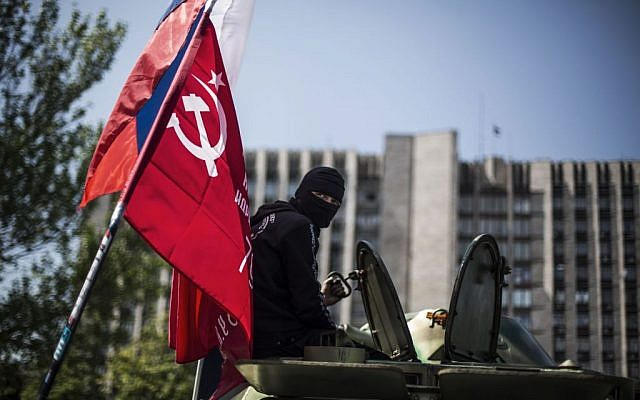 A masked pro Russia man is seen atop an APC flying a Russian flag, top, and a Donetsk People's Republic flag, as it stands in front of the occupied administration building in Donetsk, Ukraine, Saturday, May 10, 2014 (photo credit: AP/Manu Brabo)