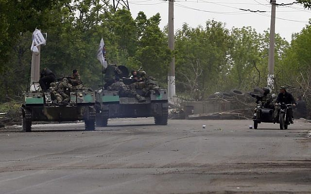 Pro-Russian gunmen atop armored personal carriers passing by barricades on a road leading into Slovyansk, eastern Ukraine, Monday, May 5, 2014.(photo credit: AP/Darko Vojinovic)