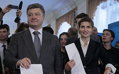 Ukrainian presidential candidate Petro Poroshenko, left, and his wife Maria, right, cast their ballots at a polling station during the presidential election in Kiev, Ukraine, Sunday, May 25, 2014. (photo credit: AP Photo/Sergei Chuzavkov)