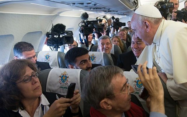 In this photo provided by the Vatican newspaper L'Osservatore Romano, Pope Francis greets journalists aboard the papal flight to Amman, Jordan, Saturday, May 24, 2014. (Photo credit: AP/L'Osservatore Romano, ho)