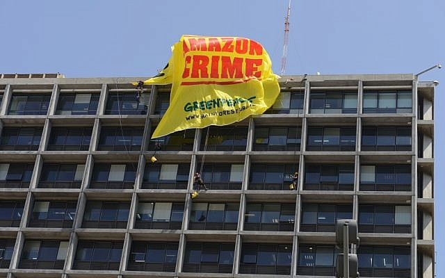 Greenpeace activists repel from the roof of Tel Aviv city hall, May 28, 2014, to hang a 200 square meter (yards) banner encouraging Mayor Ron Huldai to stop the city's policy of using controversial timber from the Amazon rainforest for city projects. (photo credit: Greenpeace/courtesy)