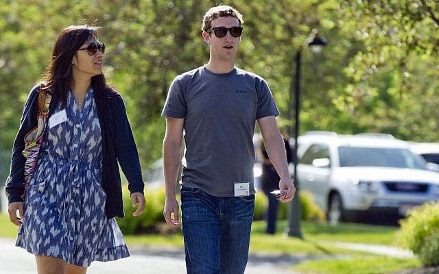 In this July 9, 2011, file photo, Mark Zuckerberg, president and CEO of Facebook, walks to morning sessions with his then girlfriend Priscilla Chan during the 2011 Allen and Co. Sun Valley Conference, in Sun Valley, Idaho. (Photo credit: AP/Julie Jacobson)