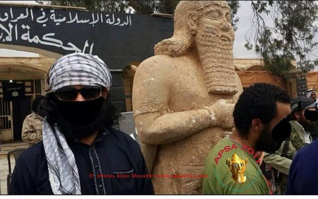 Members of the Islamic State of Iraq and the Levant stand in front of an Assyrian statue before destroying it (photo courtesy of APSA/Abou Mouseb)