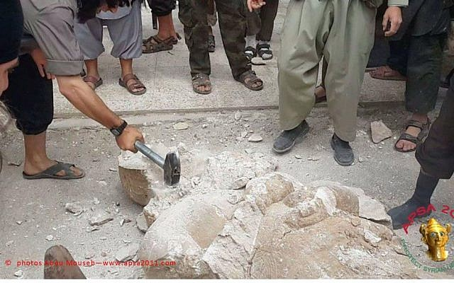 Members of the Islamic State of Iraq and the Levant smash an Assyrian statue. (photo courtesy of APSA/Abou Mouseb)