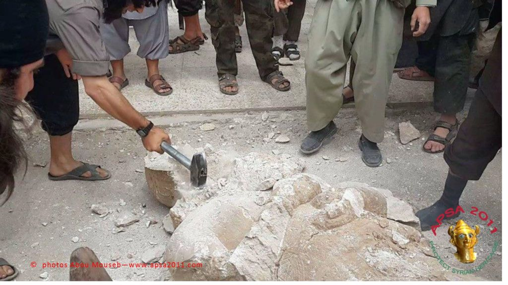 Members of the Islamic State of Iraq and the Levant smash an Assyrian statue in Mosul, Iraq. (photo courtesy of APSA/Abou Mouseb)