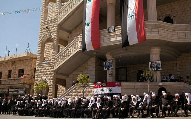 Druze residents of the Golan Heights hold Syrian flags and portraits of Syria's President Bashar al-Assad, during a rally in the Druze village of Majdal Shams, on Syrian Independance Day. April 17, 2012. (photo credit: Matanya Tausig/FLASH90)