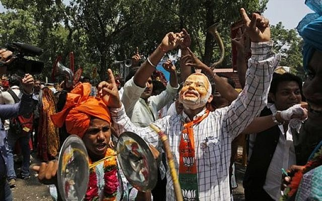 A Bharatiya Janata Party (BJP) supporter wears a mask of Narendra Modi, most likely India's next prime minister, after preliminary results showed the BJP winning by a landslide, outside the party headquarter in New Delhi, India, on Friday, May 16, 2014. (photo credit: AP/Manish Swarup)