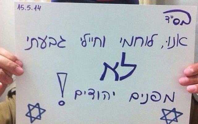 An anonymous IDF soldier displays a sign reading, in Hebrew, 'We, Givati warriors and soldiers, won't evacuate Jews!' on Thursday, May 15, 2014 (photo credit: News 0404/Facebook)