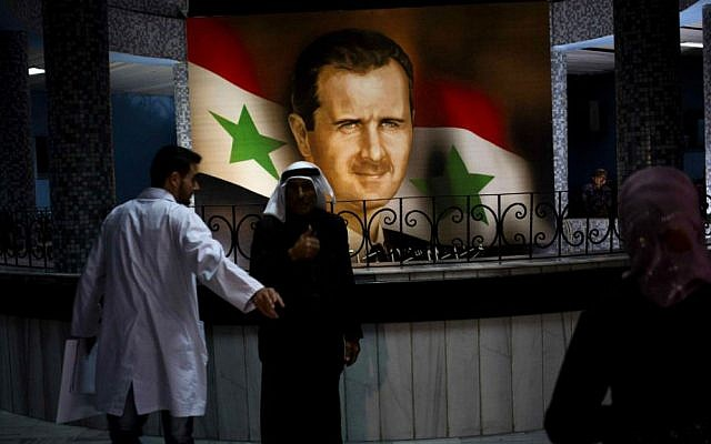 People walk through the Damascus General Hospital past a portrait of the President Bashar Assad in Damascus, Syria, Sunday, May 4, 2014.  (photo credit: AP Photo/Dusan Vranic)