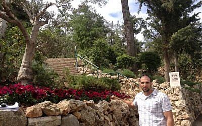 Rynkowski, alongside some petunias, a small olive tree, and one of the many stone walls, which, he said, no one knows how to rebuild (photo credit: Mitch Ginsburg/ Times of Israel)