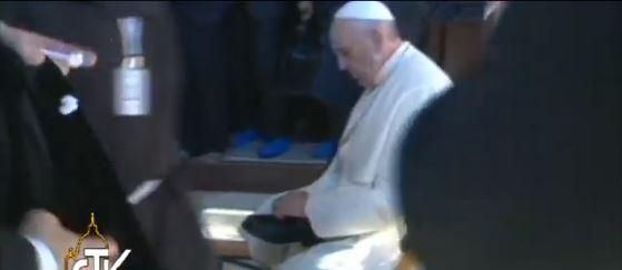 Pope Francis putting his shoes back on after visiting the Dome of the Rock. (Screen capture: Vatican TV)