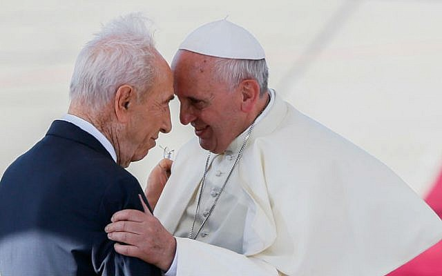 President Shimon Peres  seen embracing Pope Francis on the red carpet at a welcoming ceremony, as the pope lands at Ben Gurion international airport, May 25, 2014 (photo credit: Miriam Alster/Flash90)