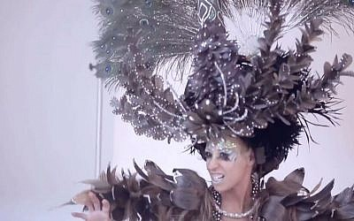 The hair peacock perched on the model's head opens its wings via remote control and breathes smoke. (YouTube screenshot)