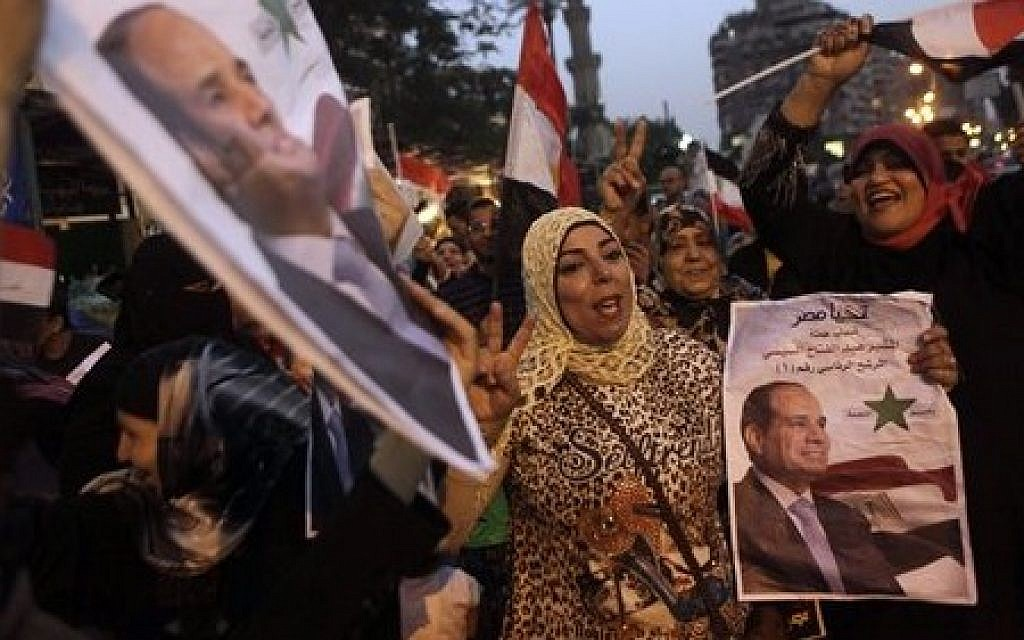Supporters of presidential candidate former army chief Abdel-Fattah el-Sissi hold his posters and wave national flags as they celebrate during the second day of presidential elections in Cairo, Egypt, Tuesday, May 27, 2014. (photo credit: AP Photo/Amr Nabil)