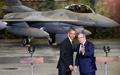 Polish President Bronislaw Komorowski (R) and US President Barack Obama address US and Polish airmen in front of a F-16 fighter jet in a hangar at Warsaw Chopin Airport, Poland, on June 3, 2014. )photo credit: AFP/Janek Skarzynski)