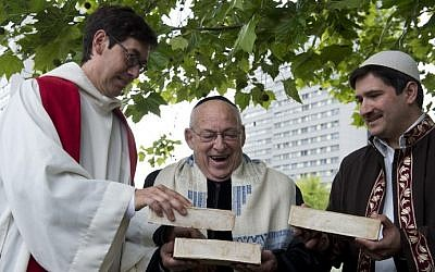 (From L) German Pastor Gregor Hohberg, Israeli Rabbi Tovia Ben-Chorin and German-Turkish Imam Kadir Sanci hold three bricks as they pose for photographers in the vacant lot where they hope to build a multifaith prayer building, in Berlin June 3, 2014 (photo credit: AFP/JOHN MACDOUGALL)