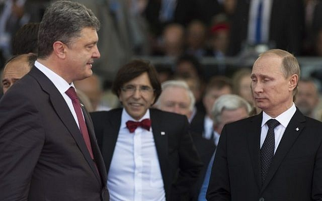 Ukraine's President-elect Petro Poroshenko (L) walks past Russia's President Vladimir Putin (R) during an international D-Day commemoration ceremony on the beach of Ouistreham, Normandy, on June 6, 2014, marking the 70th anniversary of the World War II Allied landings in Normandy. (photo credit: Alexander Zemlianichenko/AFP)