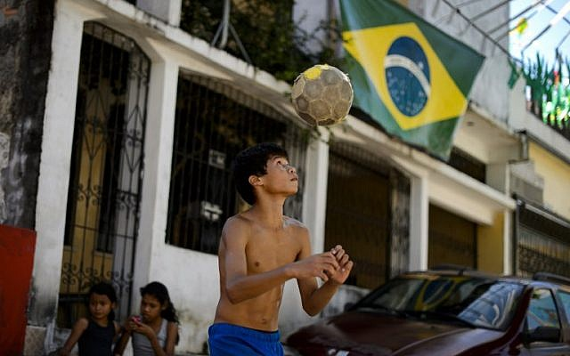 A young resident juggles a football in front of a Brazilian flag in Manaus on June 14, 1014.(photo credit: AFP/FABRICE COFFRINI)