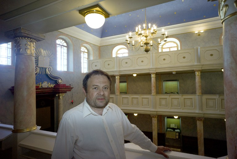 "Jan Kindermann, head coordinator of the EU-sponsored ""10 Stars"" project that revamps 15 Jewish sites in 10 places across the Czech Republic, poses for a photo in the synagogue in Brandys and Labem town on June 6, 2014. (photo credit: AFP/Michal Cizek)"