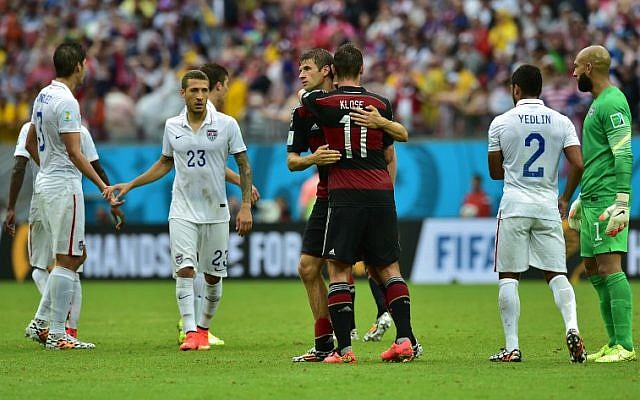 Germany's forward Thomas Mueller (C-L) hugs Germany's forward Miroslav Klose after a Group G football match between US and Germany at the Pernambuco Arena in Recife during the 2014 FIFA World Cup on June 26, 2014. (photo credit: AFP/Nelson Almeida)