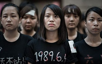 Students look ahead before singing to commemorate China's 1989 Tiananmen Square events ahead of a candlelight vigil in Hong Kong on June 4, 2014. (photo credit: Philippe Lopez/AFP)