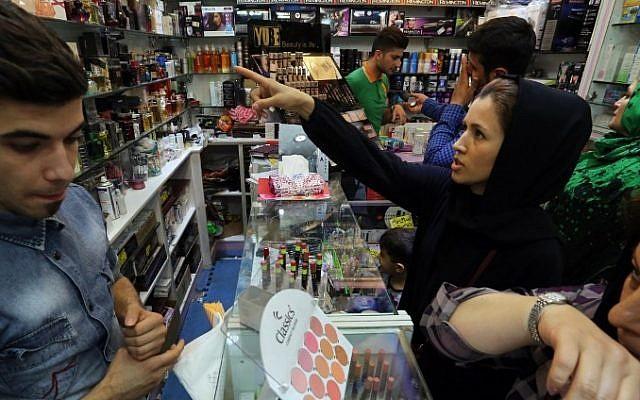 Iranian women check make up at a cosmetics shop at Tehran's Grand Bazaar on May 10, 2014.  (photo credit: AFP/Atta Kenare)