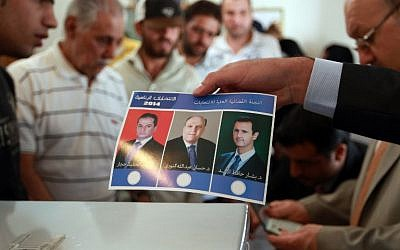 A Syrian expatriate living in Yemen holds a ballot paper bearing portraits of Syria's upcoming presidential candidates: (from L-R) Maher al-Hajjar, Hassan al-Nouri and current Syrian President Bashar al-Assad, as they cast their vote in their country's presidential elections at the Syrian embassy in Sanaa on May 28, 2014. (photo credit: AFP Photo/Mohammed Huwais)