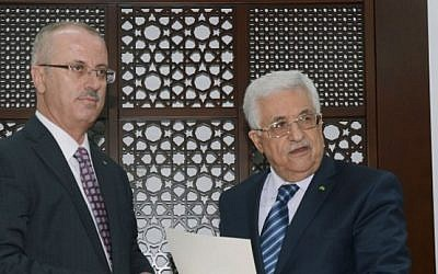 A handout picture released by the Palestinian Authority president's office shows Mahmoud Abbas (R) meeting with Palestinian premier Rami Hamdallah (L) in the West Bank city of Ramallah (photo credit: AFP PHOTO / PPO /HO)