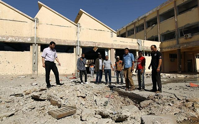 People gather at the Faculty of Mechanical Engineering Technology following an air raid that missed its target in the eastern Libyan city of Benghazi on June 1, 2014. (photo credit: AFP/ABDULLAH DOMA)