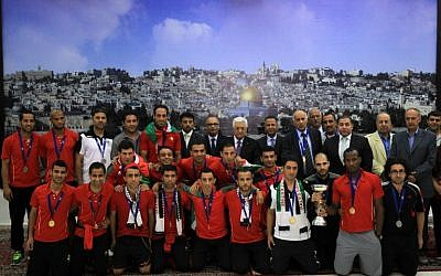 Palestinian Authority President Mahmud Abbas receives, in his office in the West Bank city of Ramallah on June 1, 2014, the Palestinian national football team which won the AFC Challenge Cup. (photo credit: AFP/Abbas Momani)