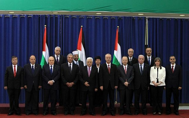 Palestinian Authority President Mahmoud Abbas (C) poses for a picture with the members of the new Palestinian unity government in the West Bank city of Ramallah, Monday, June 2, 2014 (photo credit: AFP/ABBAS MOMANI)
