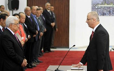 Palestinian Authority Prime Minister Rami Hamdallah (R) is sworn in along with the new Palestinian unity government in the presence of PA President Mahmoud Abbas (L) in the West Bank city of Ramallah, Monday, June 2, 2014 (photo credit: AFP/ABBAS MOMANI)