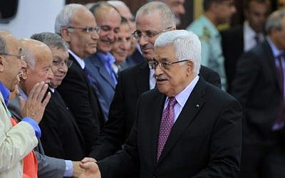 Palestinian Authority President Mahmoud Abbas and Prime Minister Rami Hamdallah greet the members of the new Palestinian unity government in the West Bank city of Ramallah, June 2, 2014. (Photo credit: AFP /ABBAS MOMANI)