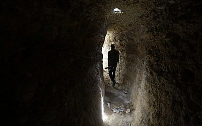 A Syrian army soldier makes his way in a tunnel reportedly previously used by rebel fighters in Jobar, a mostly rebel-held area on the eastern outskirts of Damascus on June 2, 2014. (photo credit: AFP/JOSEPH EID)