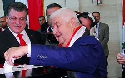 A handout picture released by the official Syrian Arab News Agency (SANA) shows Syrian Foreign Minister Walid Muallem casting his vote in the country's presidential elections at a polling station in Damascus on June 3, 2014 (Photo credit: AFP PHOTO / HO / SANA)