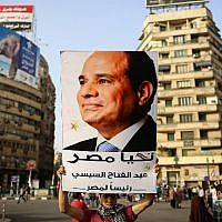 An Egyptian man holds up a portrait of ex-army chief Abdel Fattah el-Sisi as he celebrates in Cairo's Tahrir Square on June 3, 2014 after Sisi won 96.9 percent of votes in the country's presidential election (Photo credit: Mohamed el-Shahed/AFP)