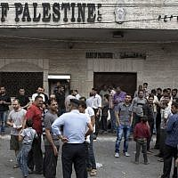 Hamas security forces in Gaza City stand guard as employees paid by the Palestinian Authority wait to receive their salaries outside a closed bank, on Thursday, June 5, 2014. (AFP/Mohammed Abed)