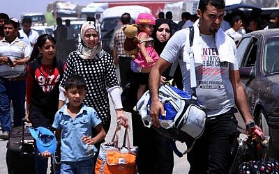 Iraqi families fleeing violence in the northern Nineveh province gather at a Kurdish checkpoint in Aski kalak, 40 kms West of Arbil, in the autonomous Kurdistan region, on June 10, 2014. (photo credit: AFP PHOTO/SAFIN HAMED)