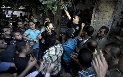 Palestinian mourners shout as the wait to carry the body of Ali al-Awour, 7, during his funeral in Beit Lahia, in the northern Gaza Strip, on Saturday, June 14, 2014. Awour, who was wounded in an Israeli air raid on June 11 in the northern Gaza Strip, died of his wounds, a spokesman for the Palestinian health services said. (photo credit: AFP/MAHMUD HAMS)