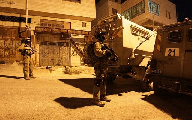 Israeli soldiers stand guard near armored vehicles as they patrol an area searching for three missing teenagers on June 15, 2014 in the West Bank town of Hebron. (photo credit: AFP/HAZEM BADER)
