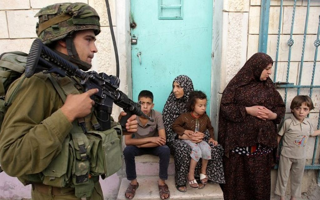 An Israeli soldier walks past Palestinians in the West Bank village of Tafoh, near Hebron on June 15, 2014, as Israeli army searches for three teenagers who went missing near a West Bank settlement. photo credit: AFP/HAZEM BADER)